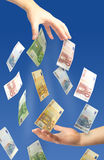 Giving euros. Hand giving money. Euro money falling on blue background Royalty Free Stock Images