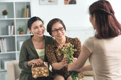 Giving flowers and presents. Vietnamese girl giving flowers and presents to her mother and grandmother Royalty Free Stock Image