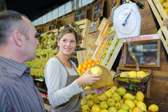 Giving fruits to client Stock Image