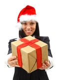 Giving a gift. Attractive businesswoman in santa hat giving a   gift to us Royalty Free Stock Photo