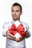 Giving a gift. Young handsome male giving a gift, over white background Stock Images