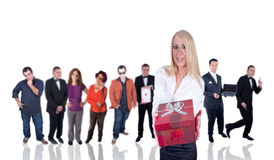 Giving the gift box. A beautiful blond woman is giving a red gift box as other people watching her Stock Images