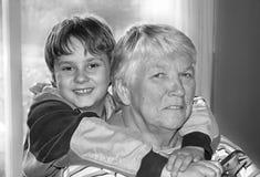 Giving grandma a hug. A grandchild giving his great grandmother a hug stock photo