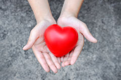 Giving heart. Heart on child hand and grunge background Stock Photo