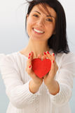 Giving Heart. Female presenting a red heart Stock Photography