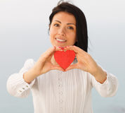 Giving Heart. Female presenting a red heart Royalty Free Stock Images