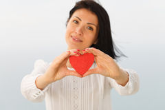 Giving Heart. Female presenting a red heart Stock Photo