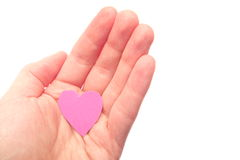 Giving heart. Hand holding a small pink paper heart, for concepts like love, care, cardiology, help, safety  or giving gifts - isolated on white Royalty Free Stock Images