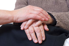 Giving help. Doctor or nurse holding elderly wrinkled hand Stock Images