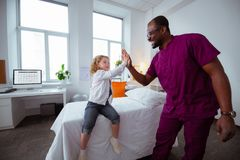 Pleasant little girl giving high five to professional pediatrician royalty free stock photo