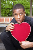 Giving His Heart. A man holding a heart shaped box Stock Images