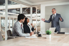 Giving his staff some experienced advice. Mature businessman standing in a boardroom giving a presentation to two work colleagues sitting a table Stock Photos