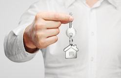 Giving house key. With house shaped keychain Royalty Free Stock Photography
