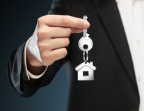 Giving house keys. Man gives keys to house on a blue background Royalty Free Stock Photo
