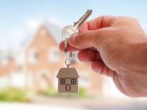 Giving house keys. Holding house keys on house shaped keychain in front of a new home royalty free stock photo