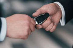 Giving a key from new car at dealership showroom.  Stock Photos