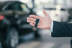 Giving a key from new car at dealership showroom.  Royalty Free Stock Photos
