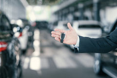 Giving a key from new car at dealership showroom.  Stock Images