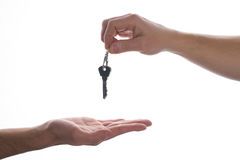 Giving key. One hand giving key to another on isolated white background. Process of buying renting selling. Agreement between two people about sales purchase royalty free stock photography
