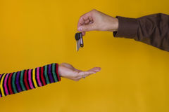 Giving Keys. A business man passing the keys to a young woman Stock Image