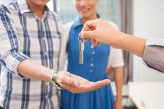 Giving keys. Hands of estate agent giving keys to the couple Stock Image