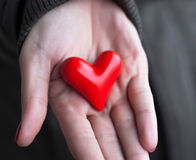 Giving love. Concept with hand holding a red heart Royalty Free Stock Photos