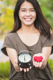 Giving love and time in valentine`s day. Asian women hand show red heart and clock. Royalty Free Stock Photos