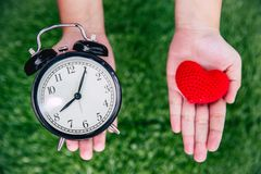 Love times heart and clock on girl hand. Giving love times heart and clock on girl hand royalty free stock image