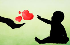 Giving love to a baby silhouette Royalty Free Stock Image