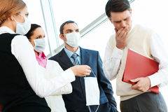 Giving mask. Group of associates in protective masks giving one to sick man royalty free stock photos