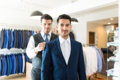 Giving Measurements For My First Bespoke Suit. Tailor taking back measurements of good looking client in order to make new suit at shop royalty free stock photos