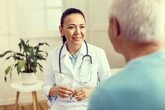 Cheerful physician talking to senior patient and smiling. Giving medical instructions. Selective focus on a mature women in a lab coat beaming while looking at a royalty free stock photos