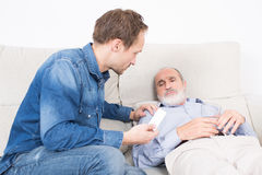 Giving medication to an elderly man Stock Photos