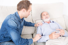 Giving medication to an elderly man. Elderly person reliefs after taking medicine Royalty Free Stock Photos