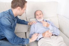 Giving medication to an elderly man. Elderly son gives medicine to his father get Stock Photo