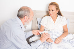Giving medication to an elderly woman Stock Photography