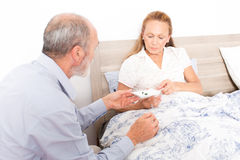Giving medication to an elderly woman Royalty Free Stock Photo