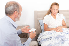 Giving medication to an elderly woman Royalty Free Stock Photos