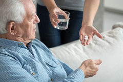 Giving the medicine. Female caregiver giving the medicine to her older male patient Stock Photos