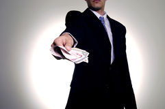 Giving the money. Man in suit with wad of money Stock Photo