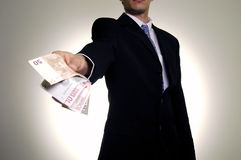 Giving the money. Man in suit with wad of money Royalty Free Stock Image