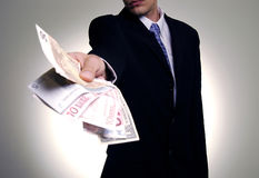 Giving the money. Man in suit with wad of money Stock Photography