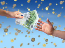 Giving money concept. Hand giving money to another hand. Coins falling on the background Royalty Free Stock Photo
