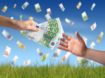 Giving money concept. Hand giving money to another hand. Money falling on the background Royalty Free Stock Photos