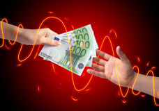 Giving money concept. Hand giving money to another hand over blue background Stock Images