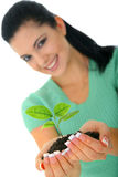 Giving New Life. Attractive woman holding new life in form of plant royalty free stock image