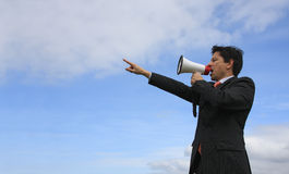 Giving an Order. A business man giving an order with a megaphone with a blue sky as Background Stock Images