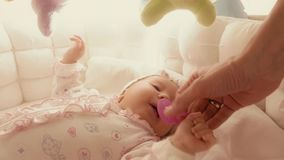 Giving pacifier to fussy baby in the cot. Newborn baby girl in her cot royalty free stock photos