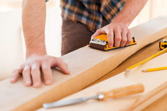 Giving perfect smoothness. Close-up of male carpenter sanding wood in his workshop Stock Image