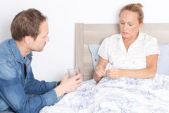 Giving pills to an elderly woman Royalty Free Stock Photos